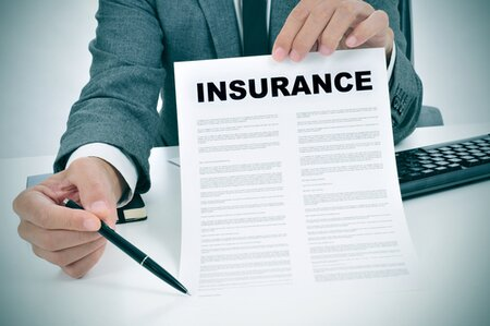 man holding insurance document